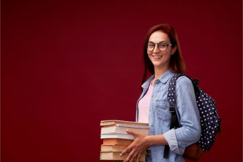 沢山の本を持つ眼鏡をかけた女性